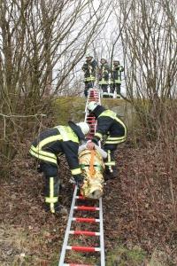 Patientin wird auf der Trage über lange Steckleiter transportiert