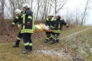 Vier Feuerwehrmänner tragen Patientin auf Trage
